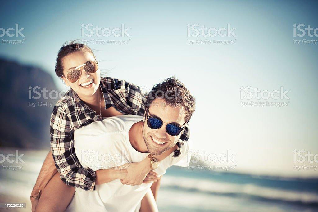 Piggyback ride at the beach stock photo