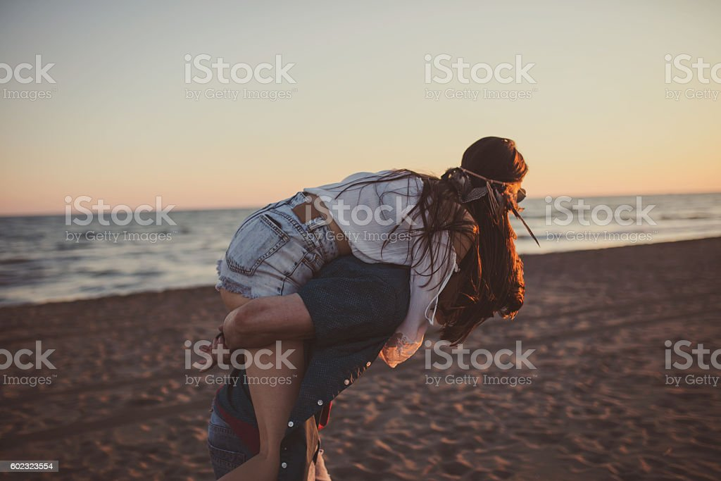 Piggyback ride on the beach, young couple stock photo