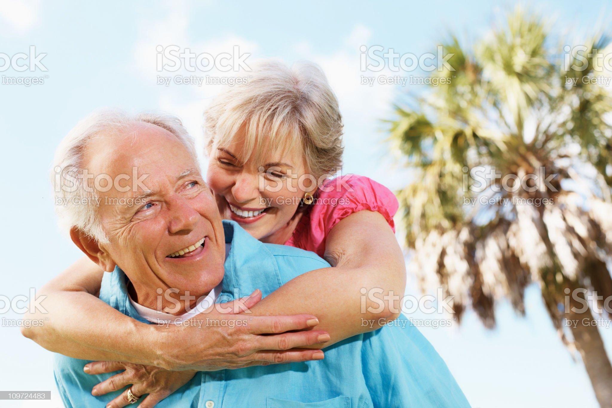 Piggybacking - Smiling mature couple enjoying themselves royalty-free stock photo