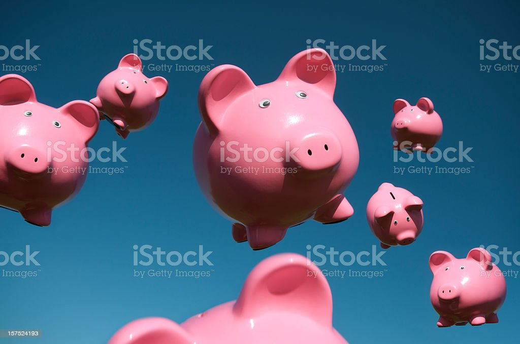 Pigs Fly in Sky Full of Flying Pink Piggy Banks stock photo