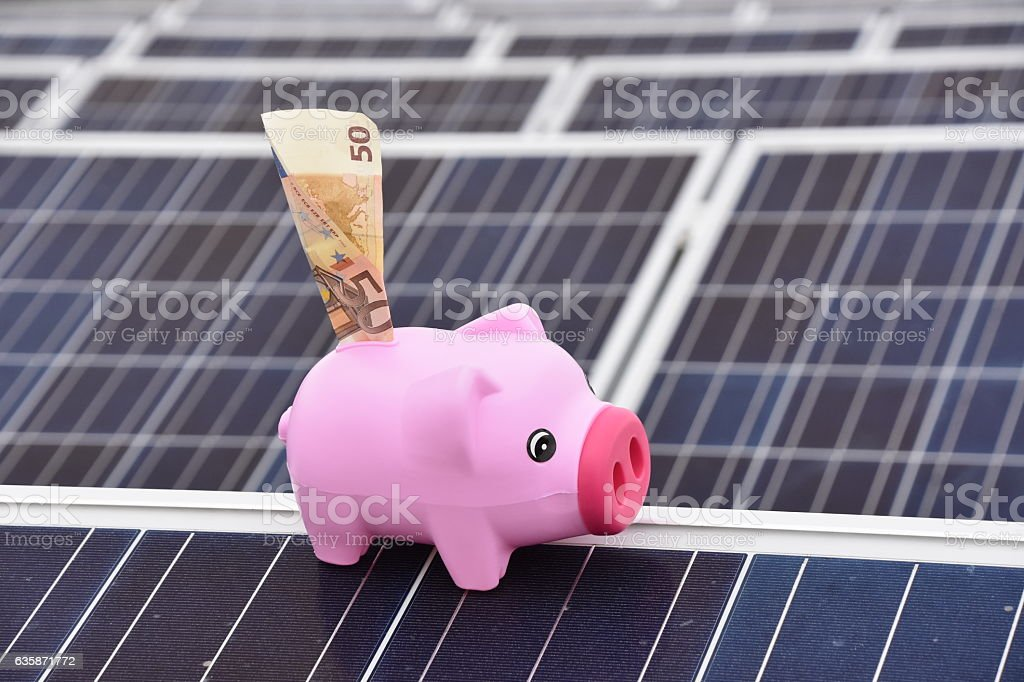 Pig-shaped piggy bank ON solar roof stock photo
