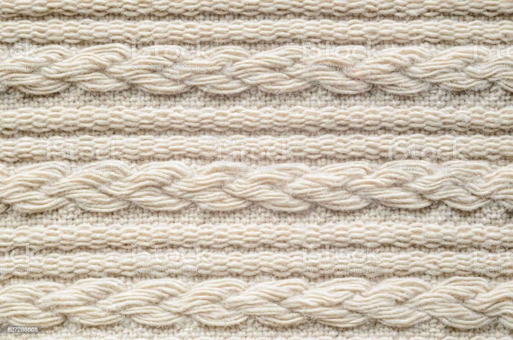 Pigtails on Beige Knitwear Fabric Texture. stock photo