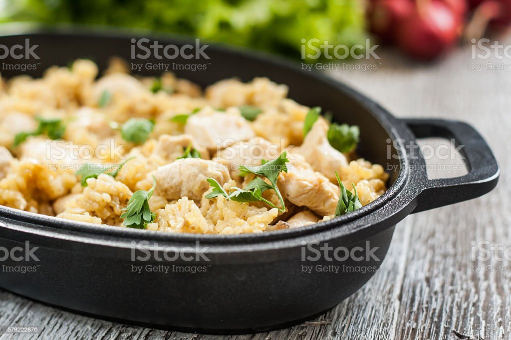Pilaf rice-curry with chicken and salad in form of iron stock photo