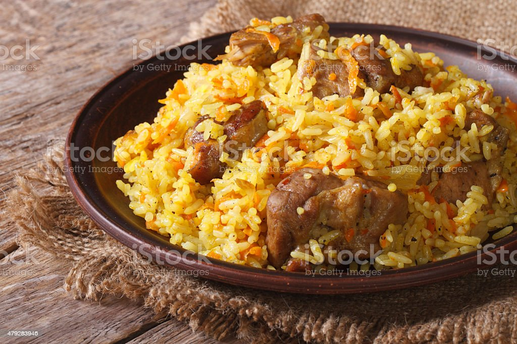 pilaf with meat and vegetables closeup on a plate. horizontal stock photo