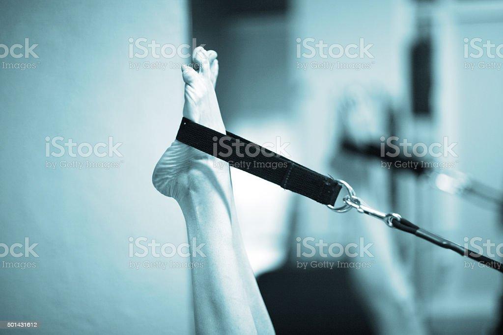 Pilates exercise fitness gym machine feet on strap stock photo