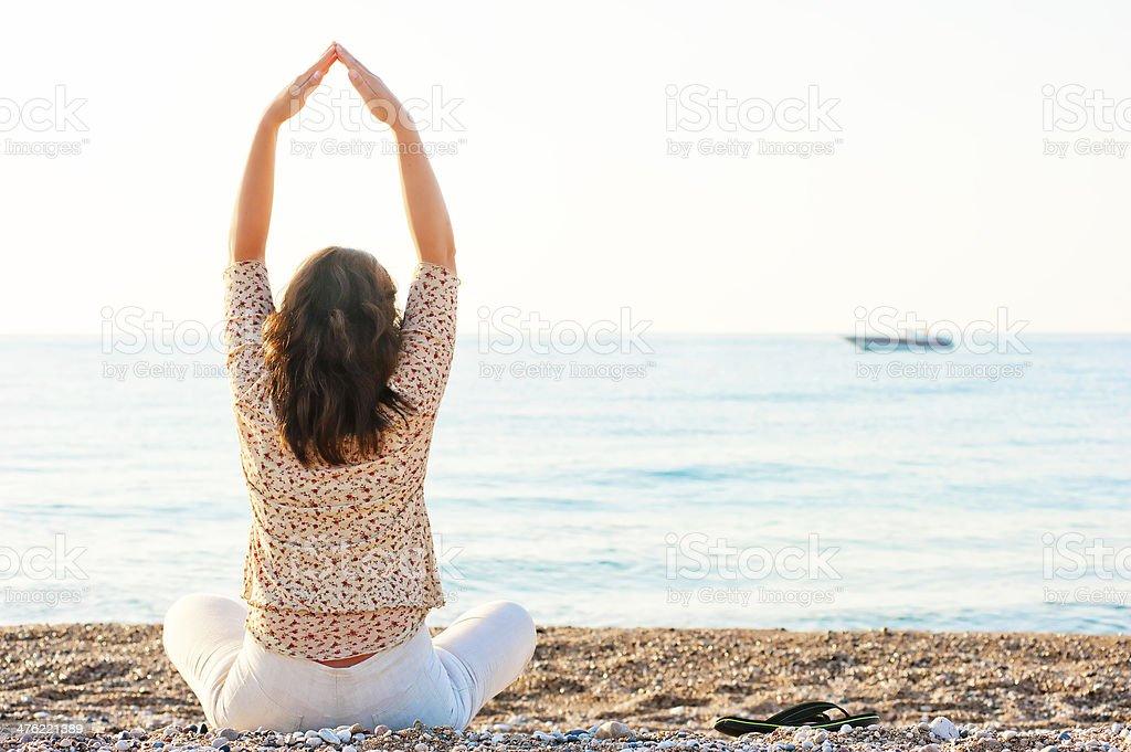 Pilates girl has sat on the beach stock photo
