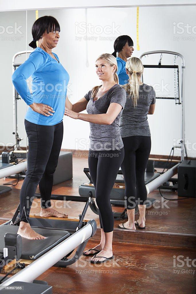 Pilates instructor helping mature woman stock photo