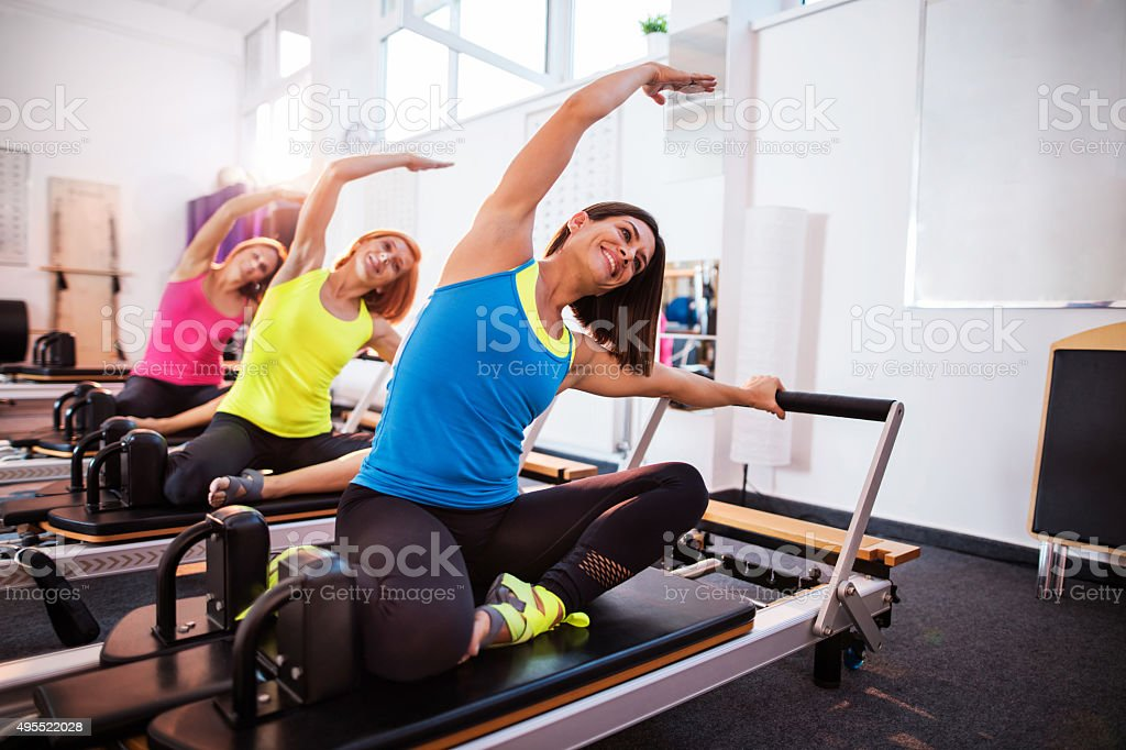 Pilates reformers doing stretching exercises on machines in health club. stock photo