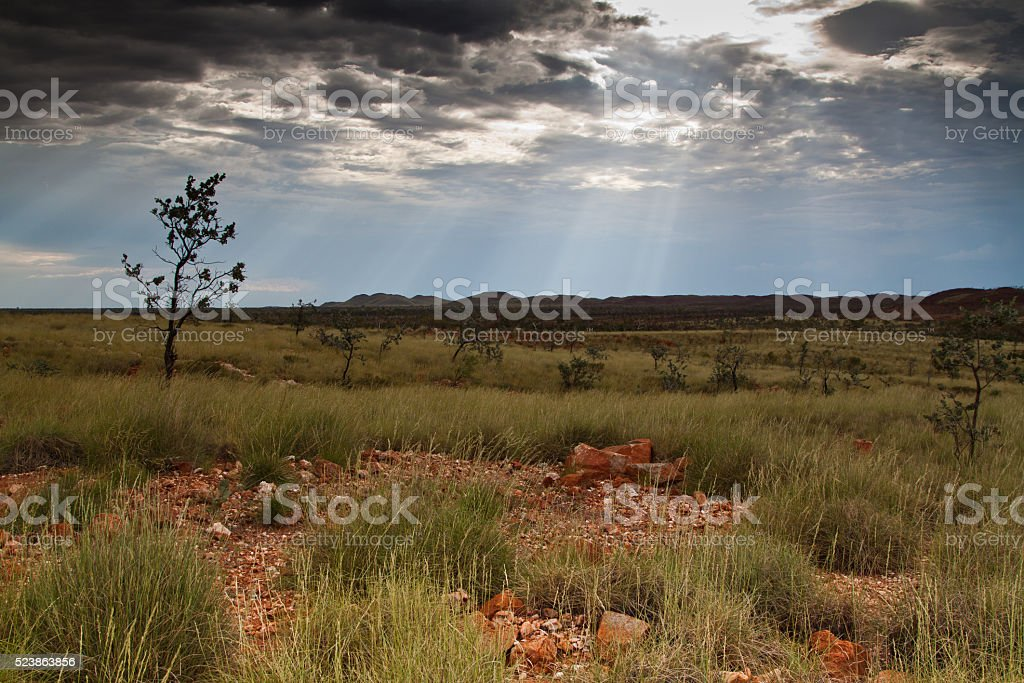 Pilbara sun rays through the clouds stock photo
