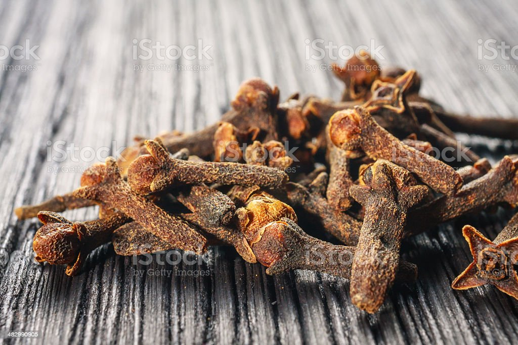 pile cloves on wood background stock photo