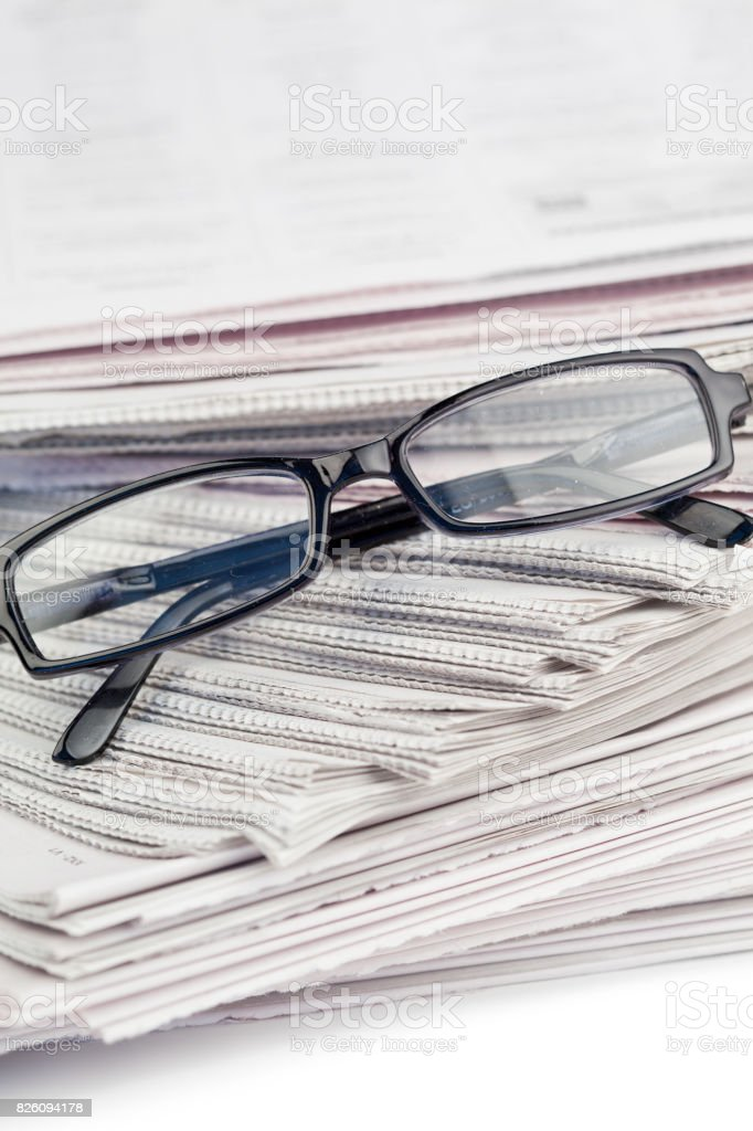 A pile newspapers and a pair of reading glasses stock photo