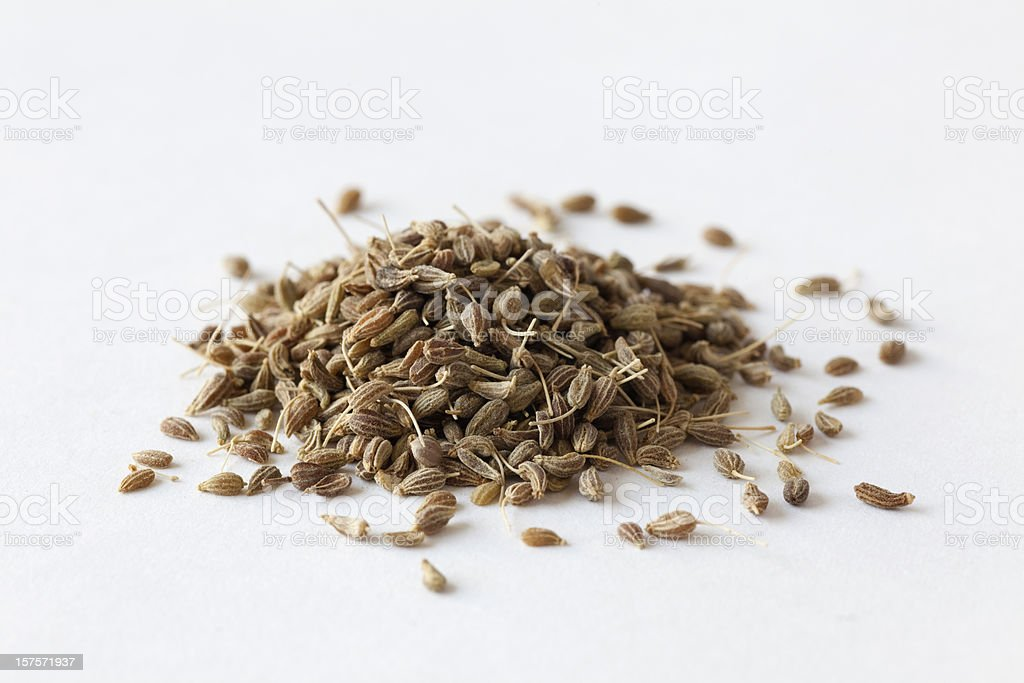Pile of anise seeds on white surface stock photo
