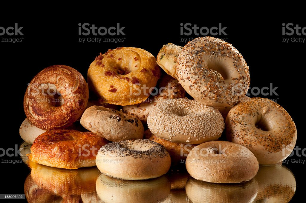 Pile of assorted bagels on reflective surface stock photo