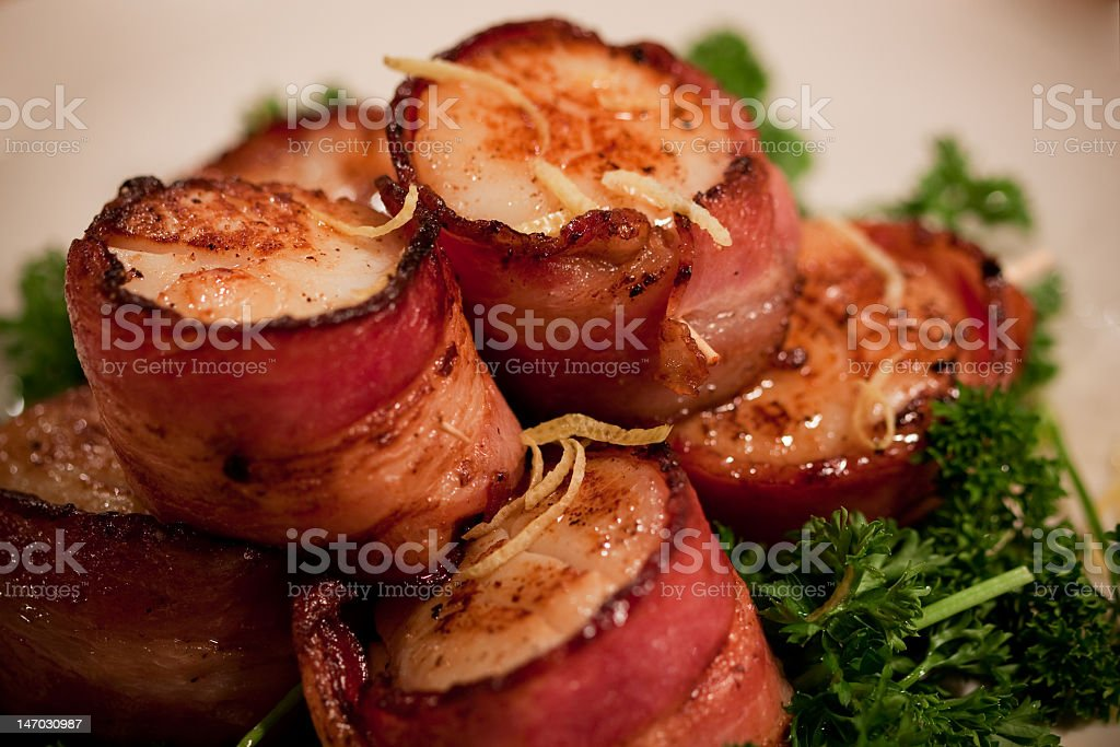 A pile of bacon wrapped scallions on a bed of greens stock photo