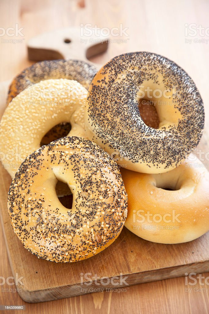 Pile of bagels on a wooden chopping board stock photo