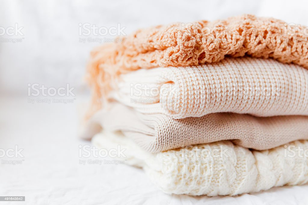 Pile of beige woolen clothes on a white background. stock photo