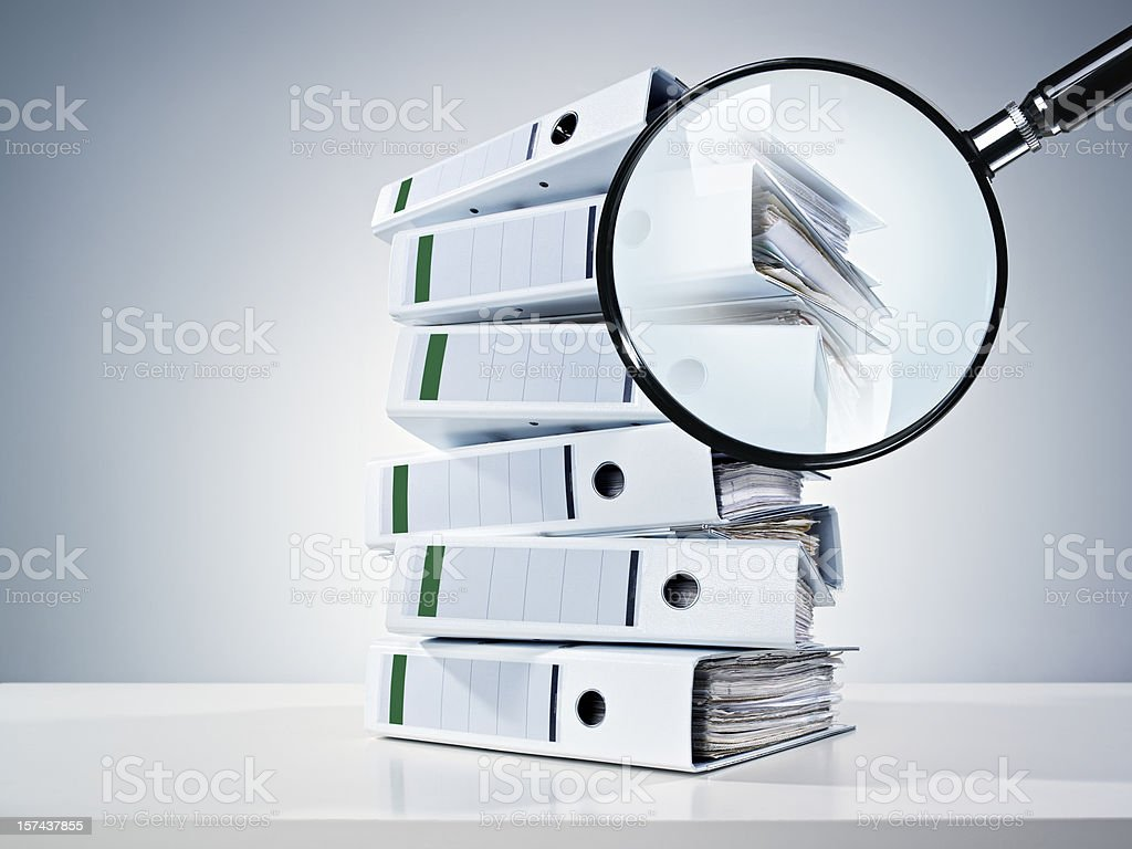 Pile of binders partially obscured by a magnifying glass stock photo