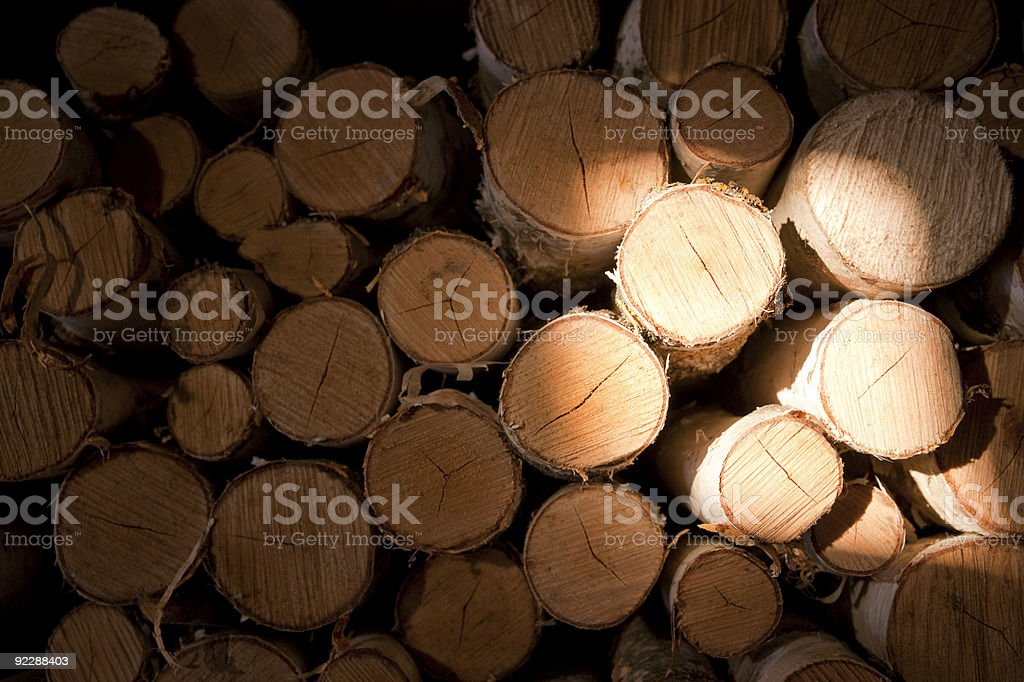 Pile of birch logs in dark with light area royalty-free stock photo