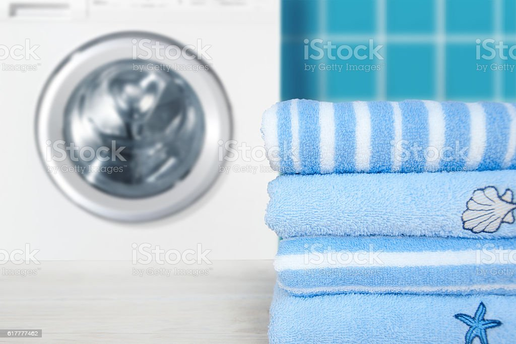 Pile of blue clean towels with washing machine. stock photo