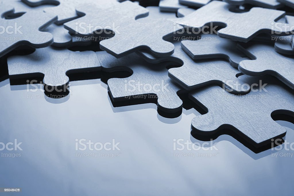 Pile of blue jigsaw puzzle pieces on similar background royalty-free stock photo