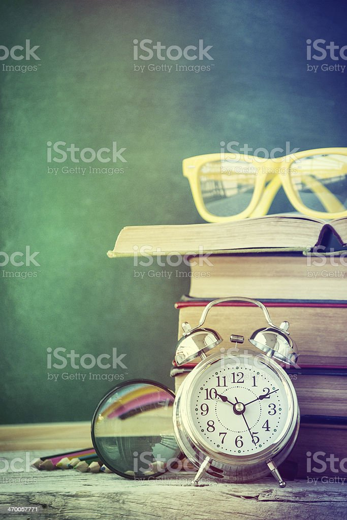 Pile of books, alarm clock, glasses, and magnifying glass royalty-free stock photo