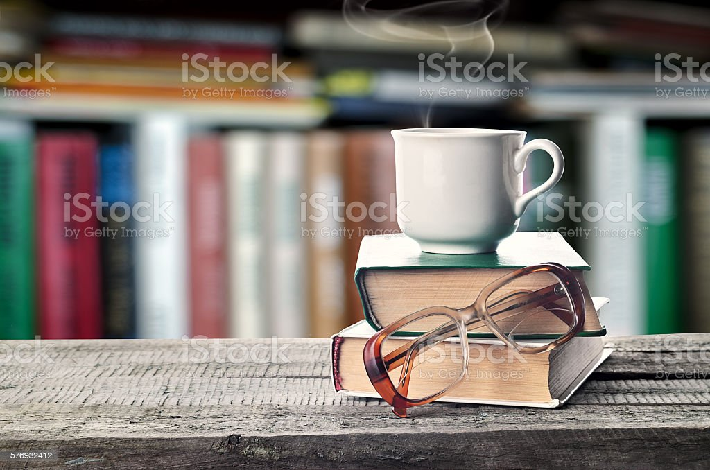 Pile of books, glasses and cup on a table stock photo