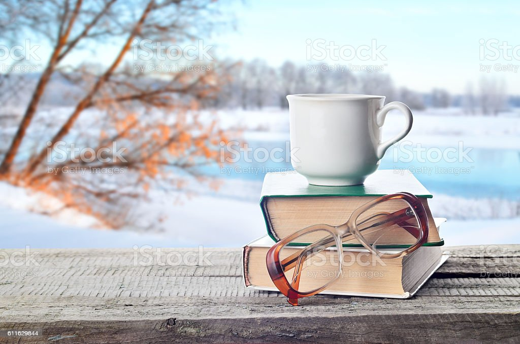 Pile of books, glasses and cup outdoors in winter stock photo