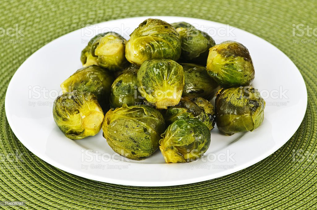 A pile of Brussel sprouts on a white plate on a green mat royalty-free stock photo