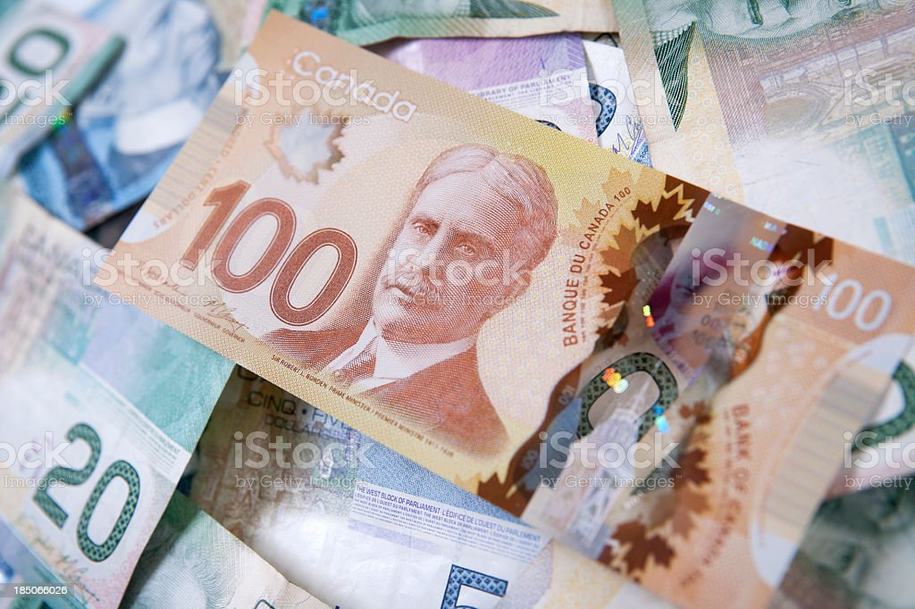 Pile of Canadian bills with one hundred dollars on top stock photo