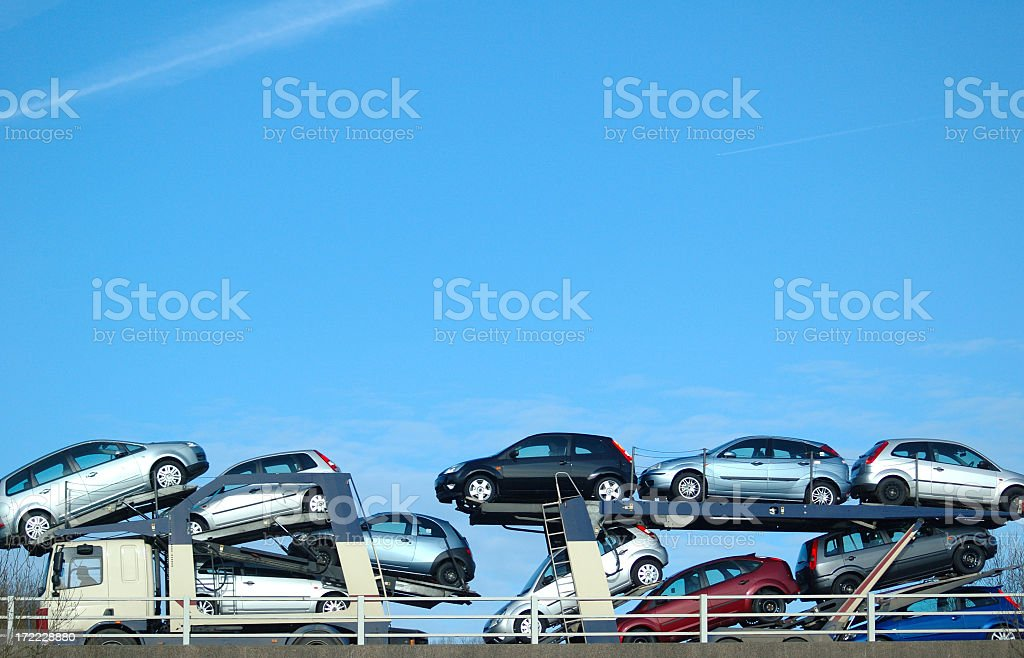 Pile of cars in a transporter over a clear blue sky stock photo
