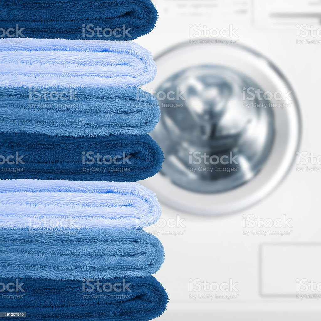 Pile of clean towels with washing machine stock photo