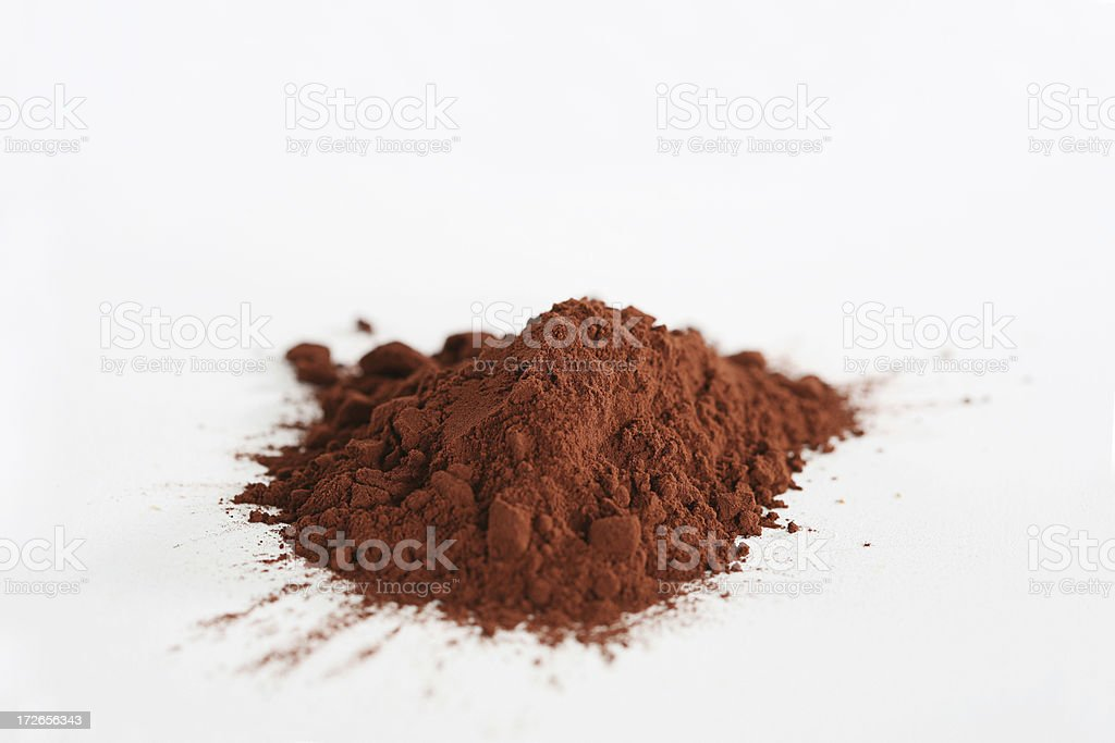 A pile of cocoa powder on a white surface stock photo