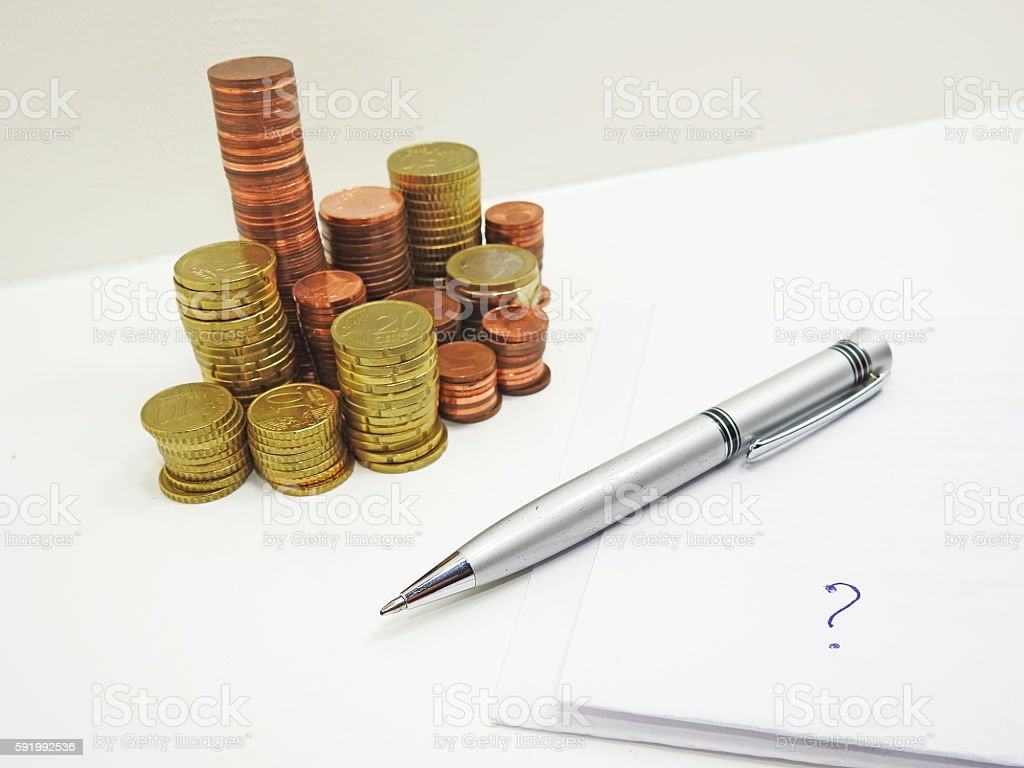 Pile of coins with pen and paper. stock photo