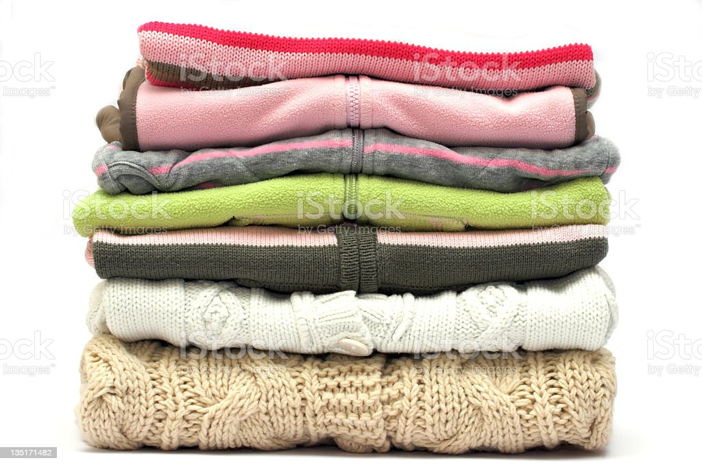 Pile of colored sweaters isolated on white  stock photo
