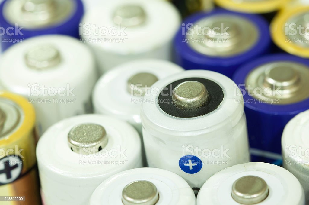 Pile of colorful batteries stacked in a row together stock photo
