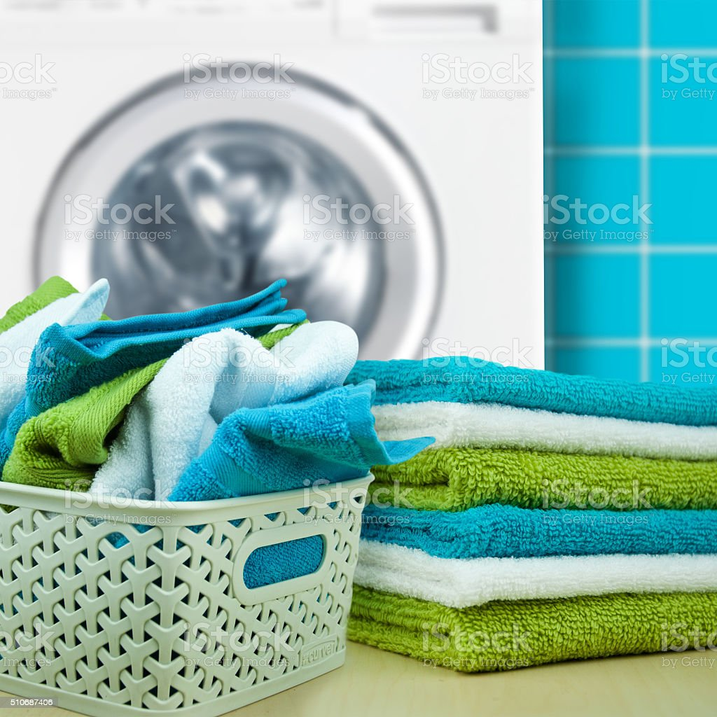 Pile of colorful clean towels with washing machine stock photo