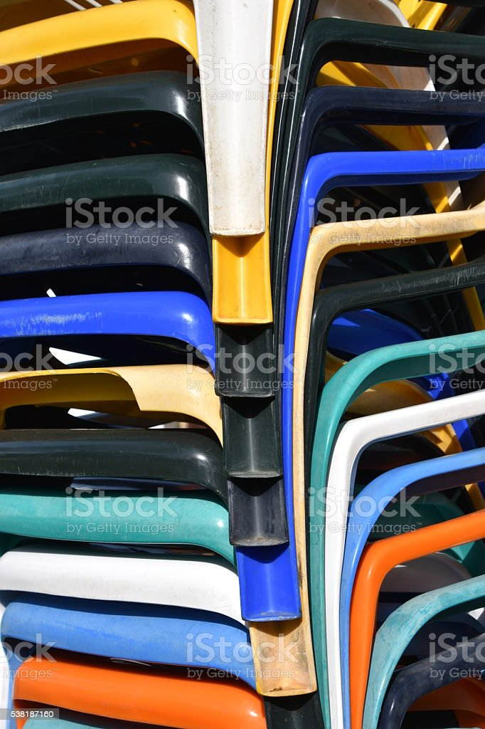 pile of colorful plastic chairs stock photo