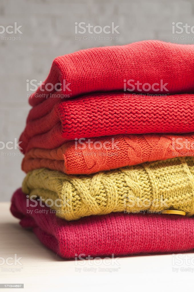 pile of colorful sweaters stock photo