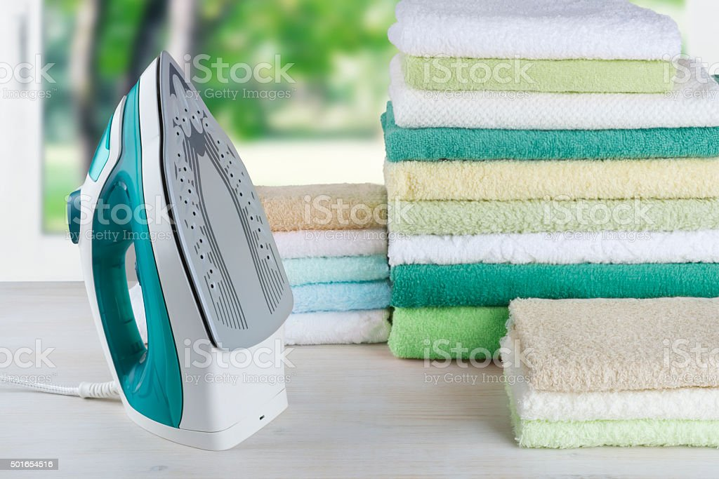 Pile of colorful towels and electric iron, ironing clothes concept stock photo