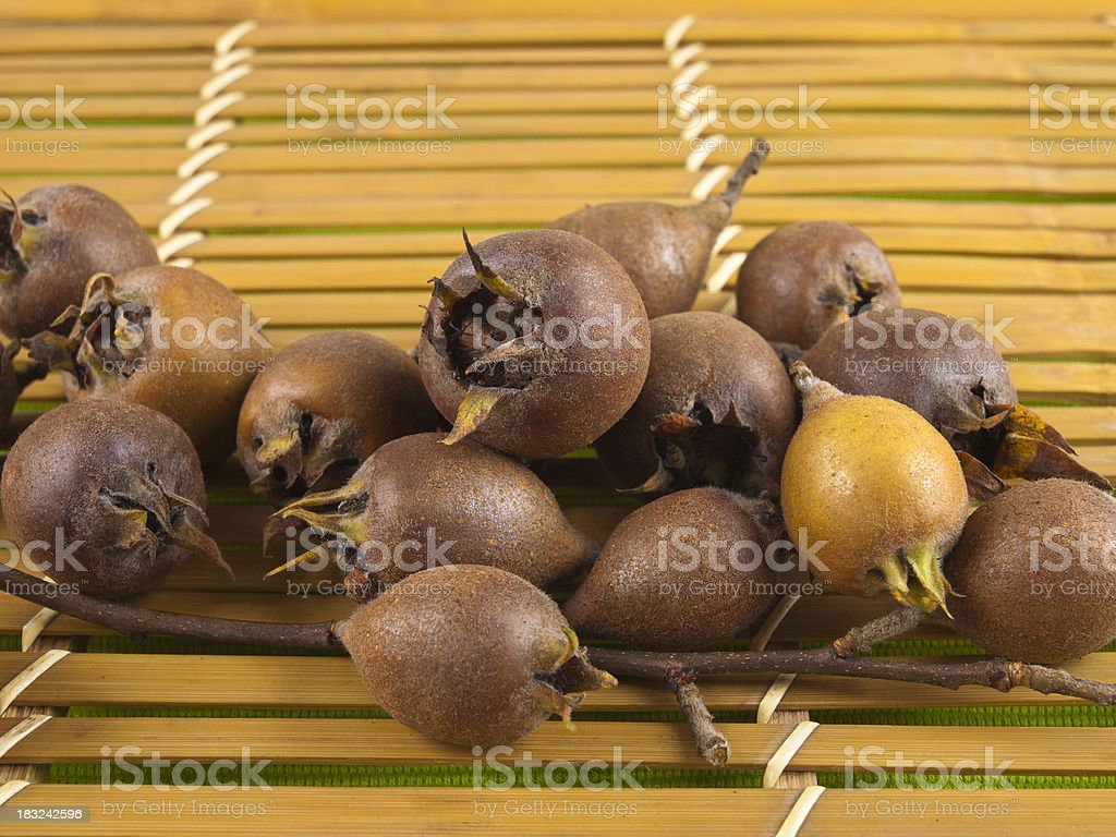 Pile of Common Medlar on top of Wooden Slats stock photo