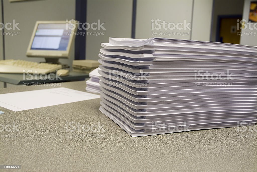 Pile of copies with screen in background royalty-free stock photo