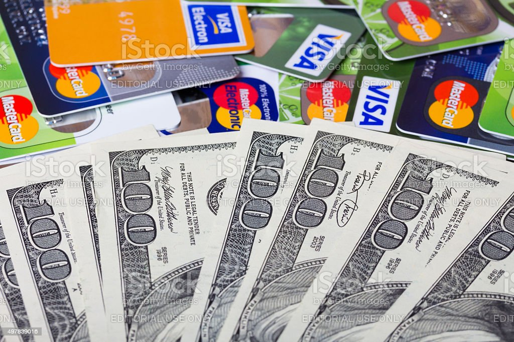 Pile of credit cards and dollar bills stock photo
