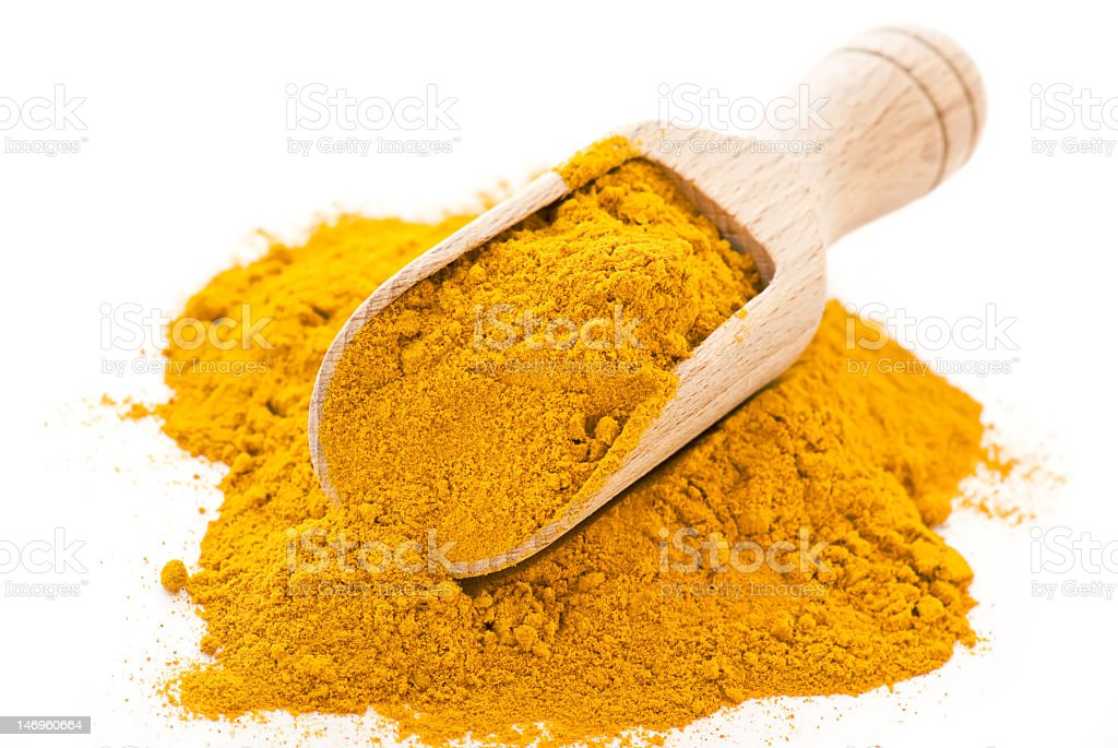 A pile of curry powder with a scoop in it royalty-free stock photo