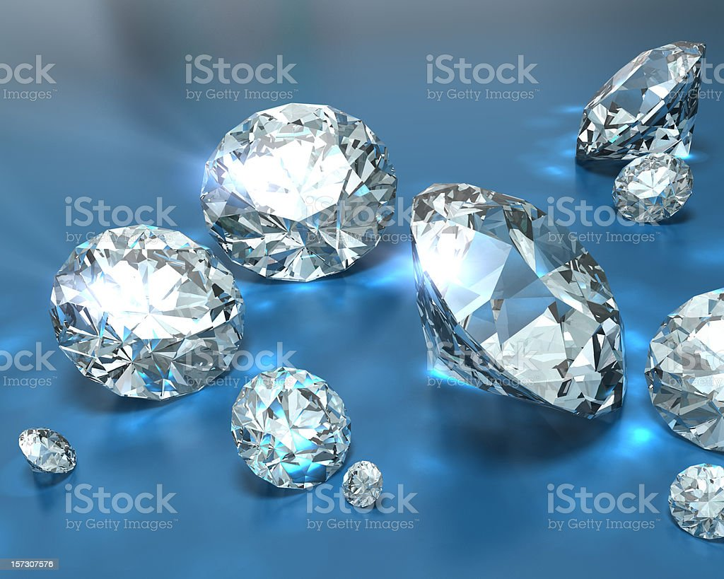 A pile of diamonds of various sizes on a blue background stock photo