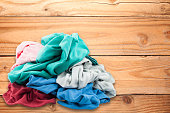 Pile of dirty colorful clothes on wooden floor .