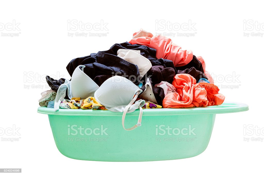 Pile of dirty laundry in a washing basket on  white stock photo