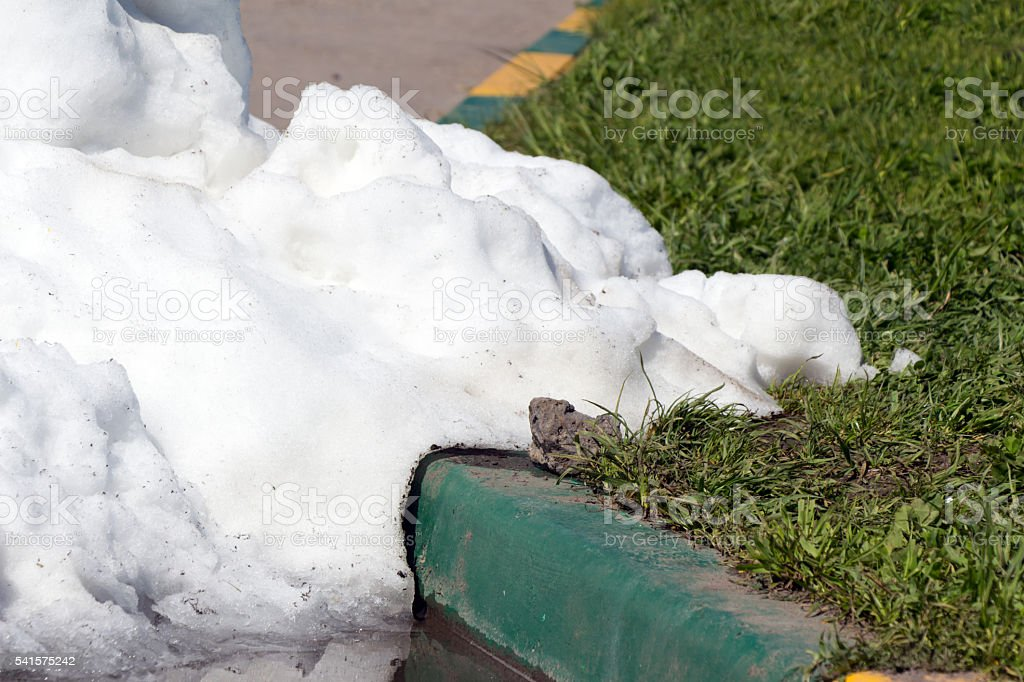 Pile of dirty snow lying on the road stock photo