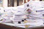 Pile of documents on desk stack up high waiting