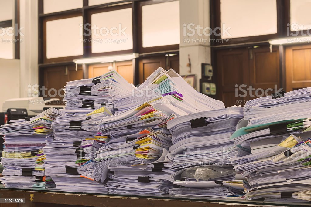 Pile of documents on desk stack up high waiting stock photo