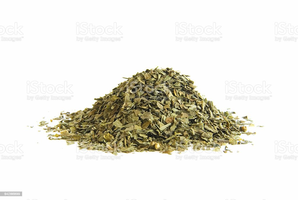 Pile of dried basil leaves on white royalty-free stock photo